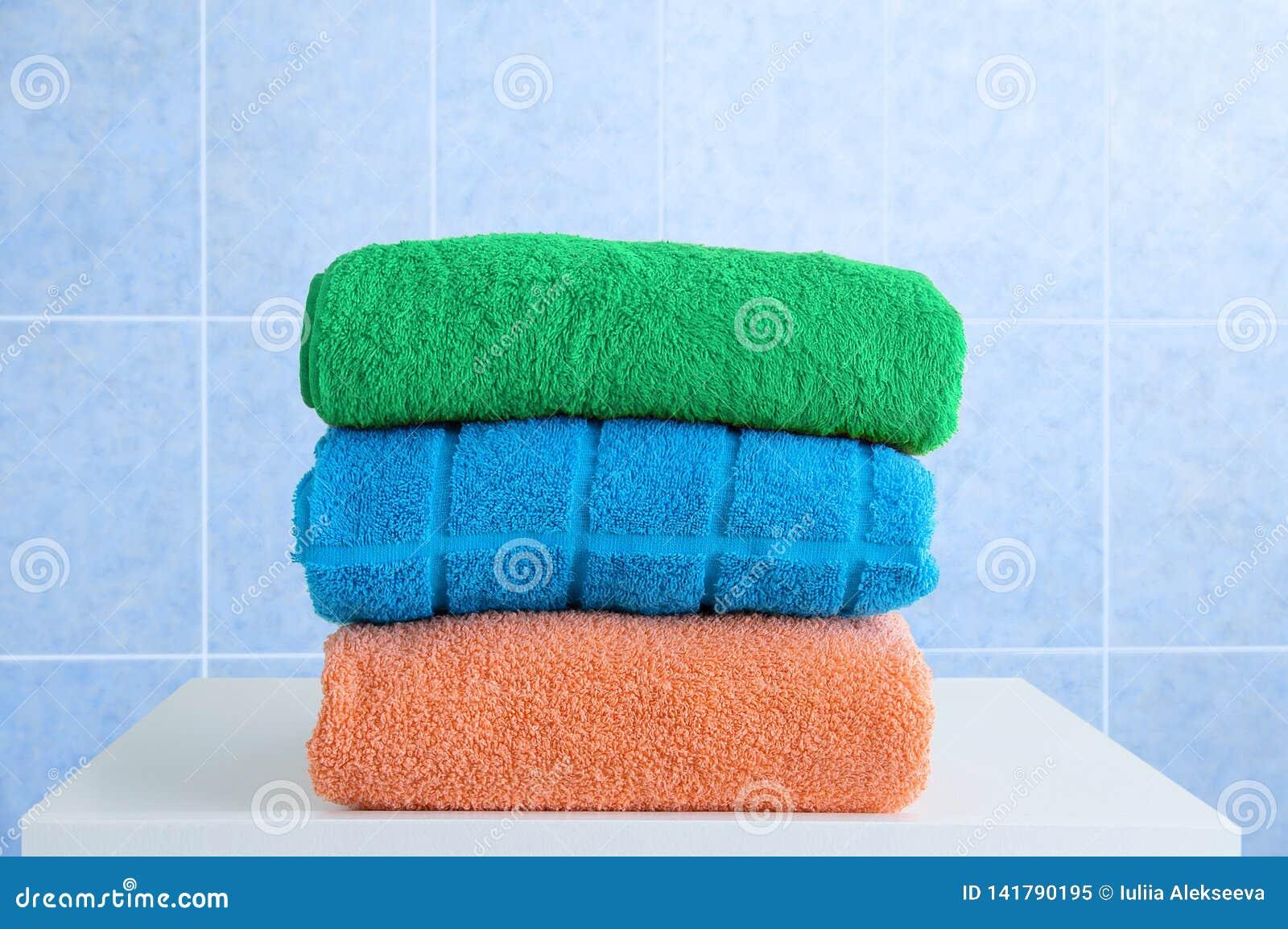 Terry handdoeken op een witte nightstand in badkamers Blauwe tegel als achtergrond