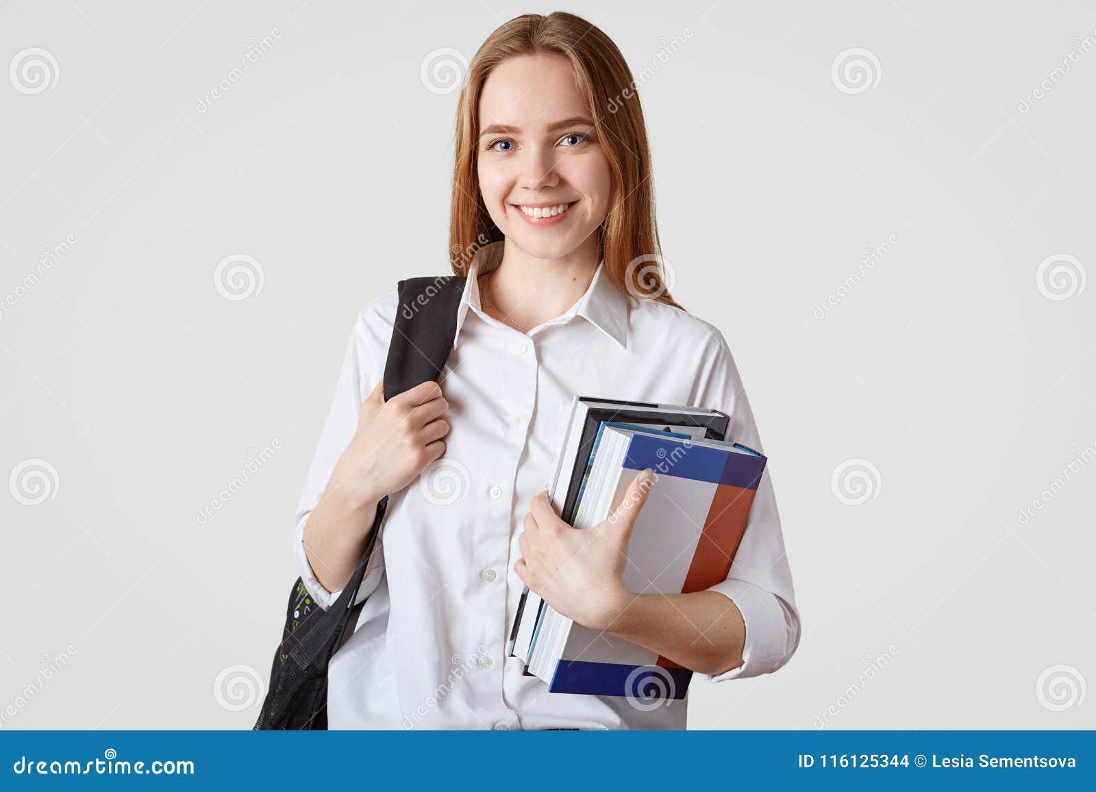 Terug naar het Concept van de School Glimlachend Europees schoolmeisje in elegante kleren, draagt rugzak en stapel van boeken, bl