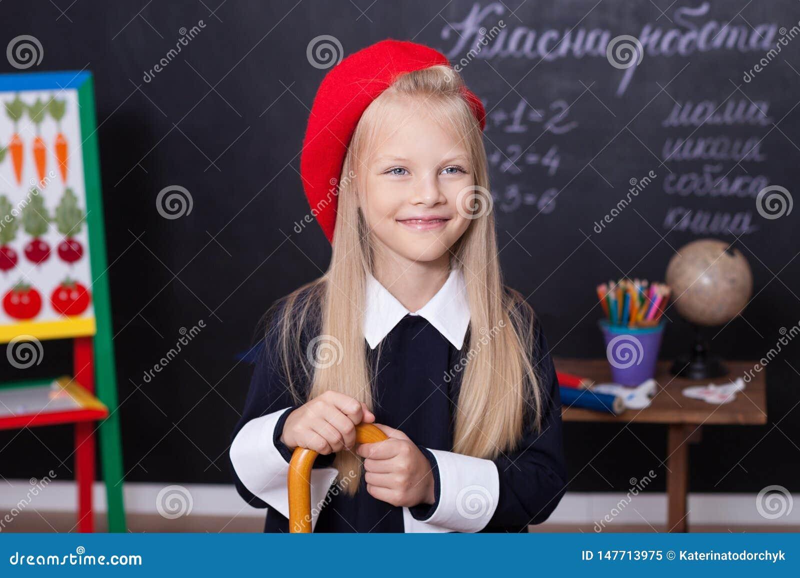 Terug naar school! Een schoolmeisje bevindt zich bij het bord met een heerser Een schoolmeisje beantwoordt de les Een eerste-nive