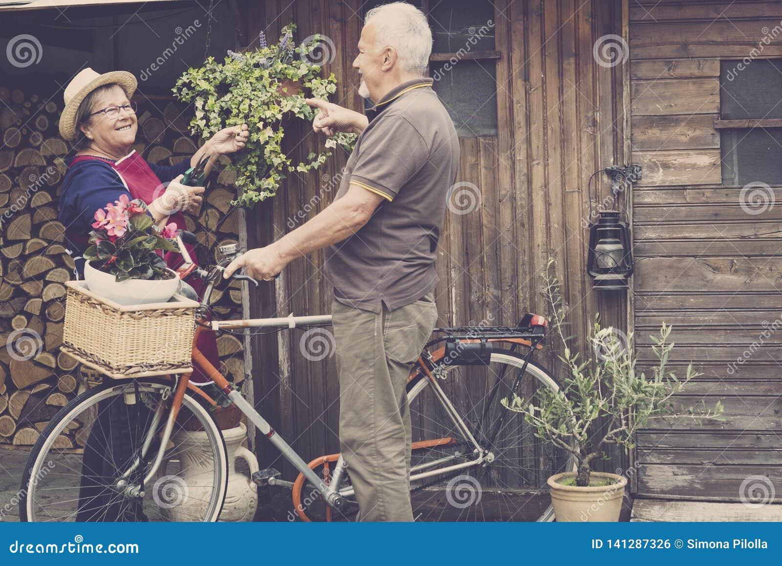 Teruggetrokken volwassen Kaukasisch paarverblijf in jardin bij zijn eigen huis om aan de installaties en de groenten te werken ou