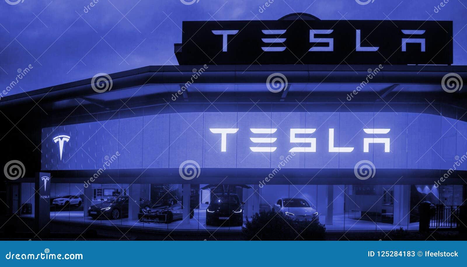 Tesla едет на автомобиле выставочный зал с автомобилями внутри и загоренными отрубями логотипа