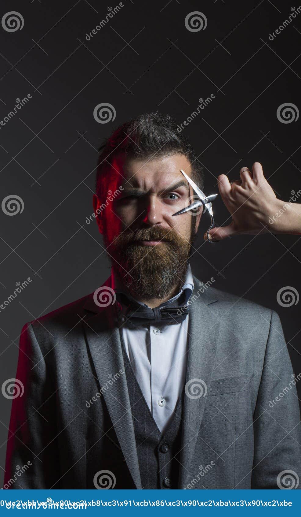 Tesouras do barbeiro Corte de cabelo dos homens Homem farpado, barba longa, moderno brutal, caucasiano com bigode, corte de cabel