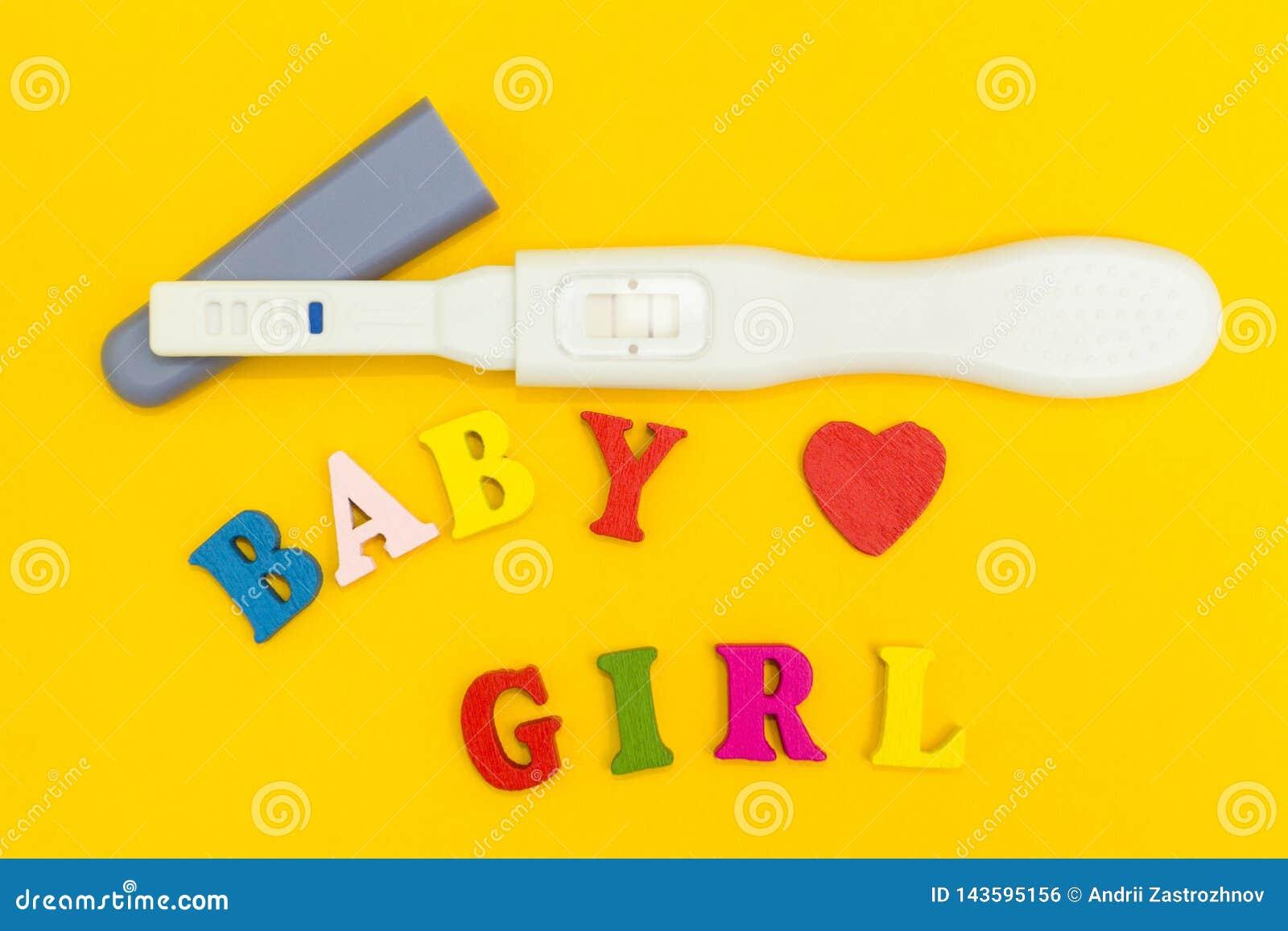 Teste de gravidez positivo, coração e a palavra 'bebê e menina 'em um fundo amarelo