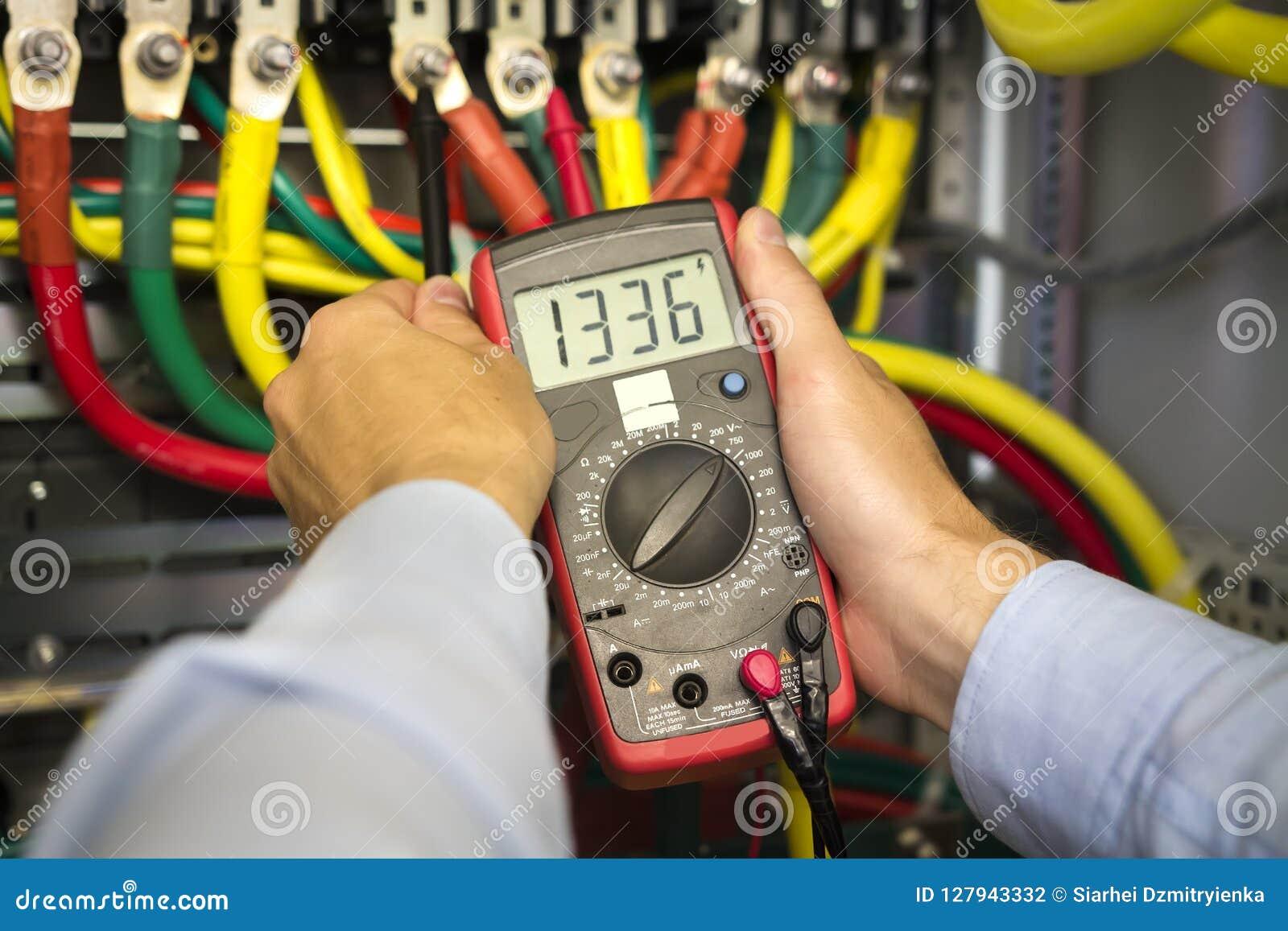 Tester elettrico in mani del primo piano dell ingegnere Tecnico dell elettricista sul lavoro che ispeziona il collegamento di cab