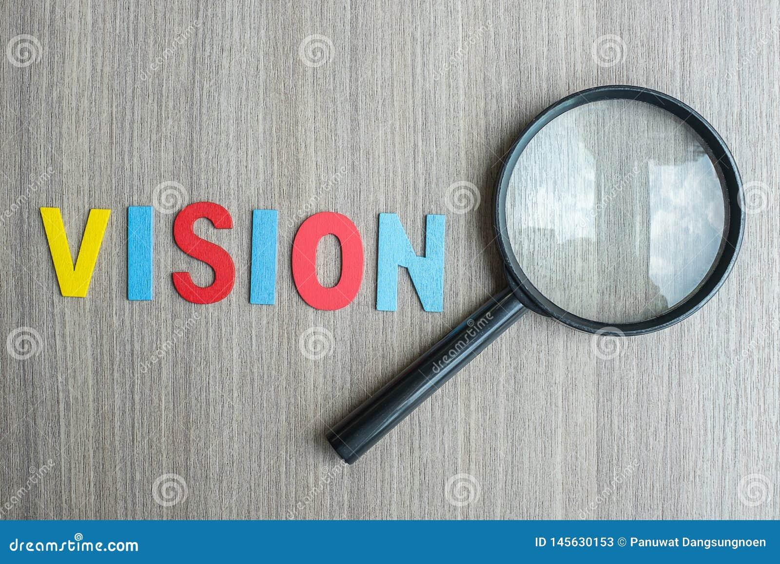 Testo di VISIONE sulla nota gialla con carta e la lente d ingrandimento sbriciolate sul fondo di legno della tavola SEO, idea, so