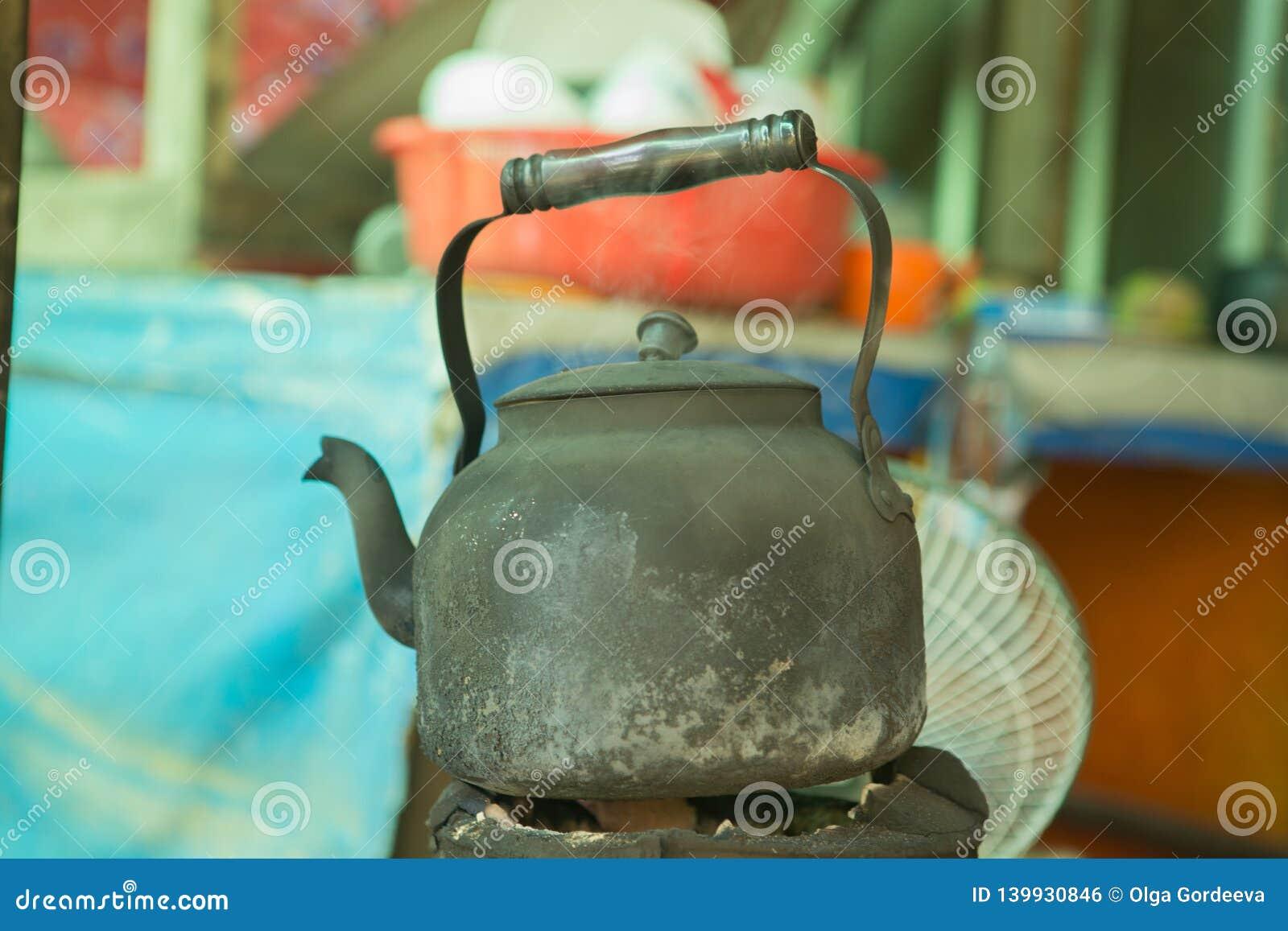 Tetera vieja en el hollín, agua de la ebullición, hollín