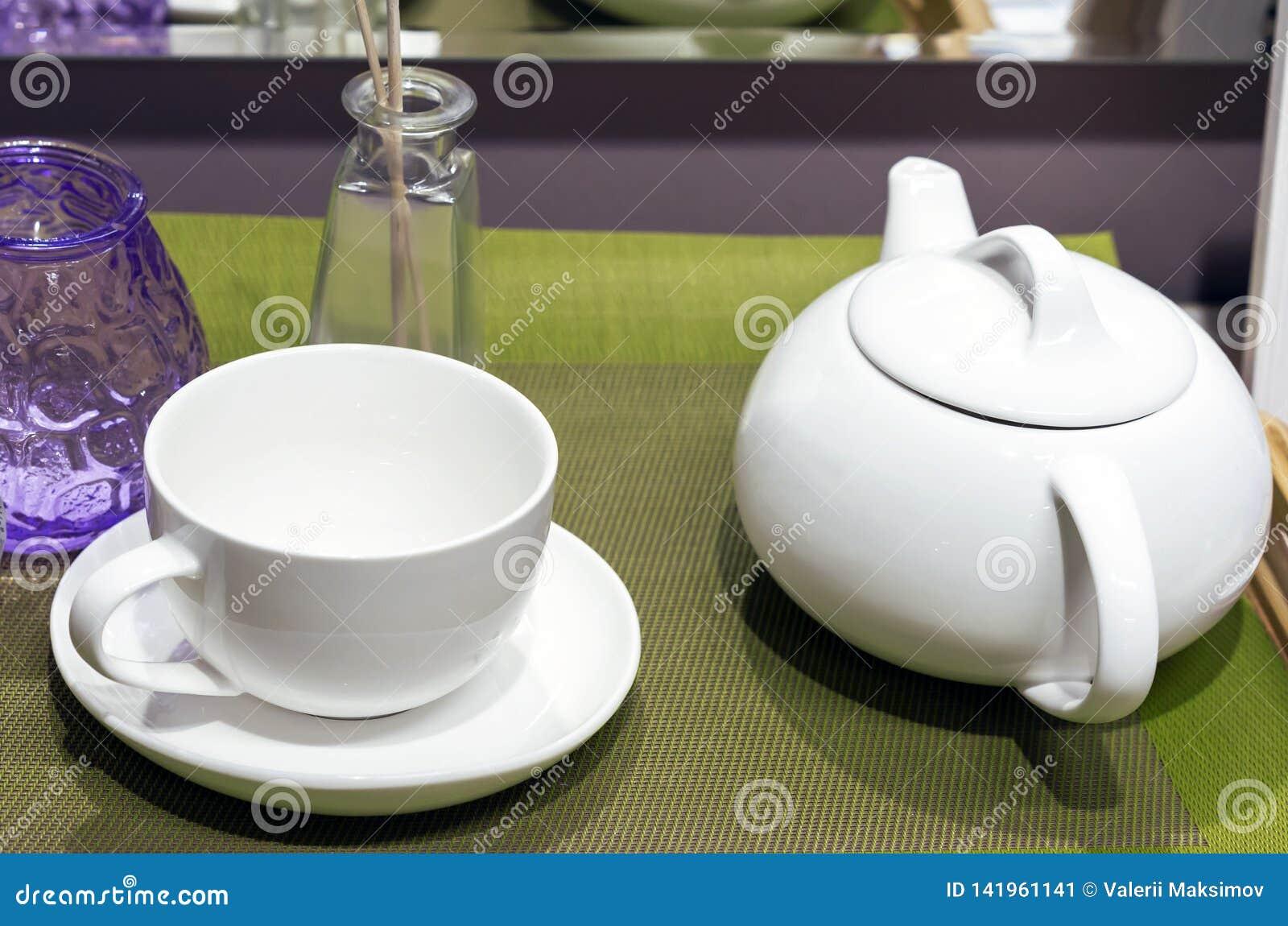 Tetera y taza de cerámica blancas en una servilleta verde
