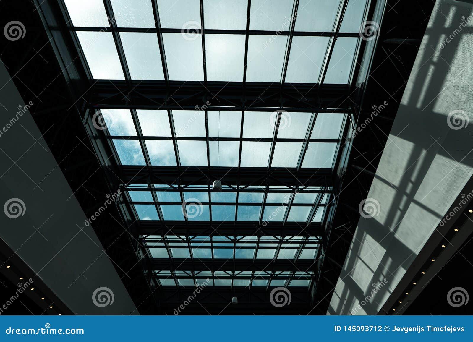 Teto de vidro em um shopping com um sol brilhante fora