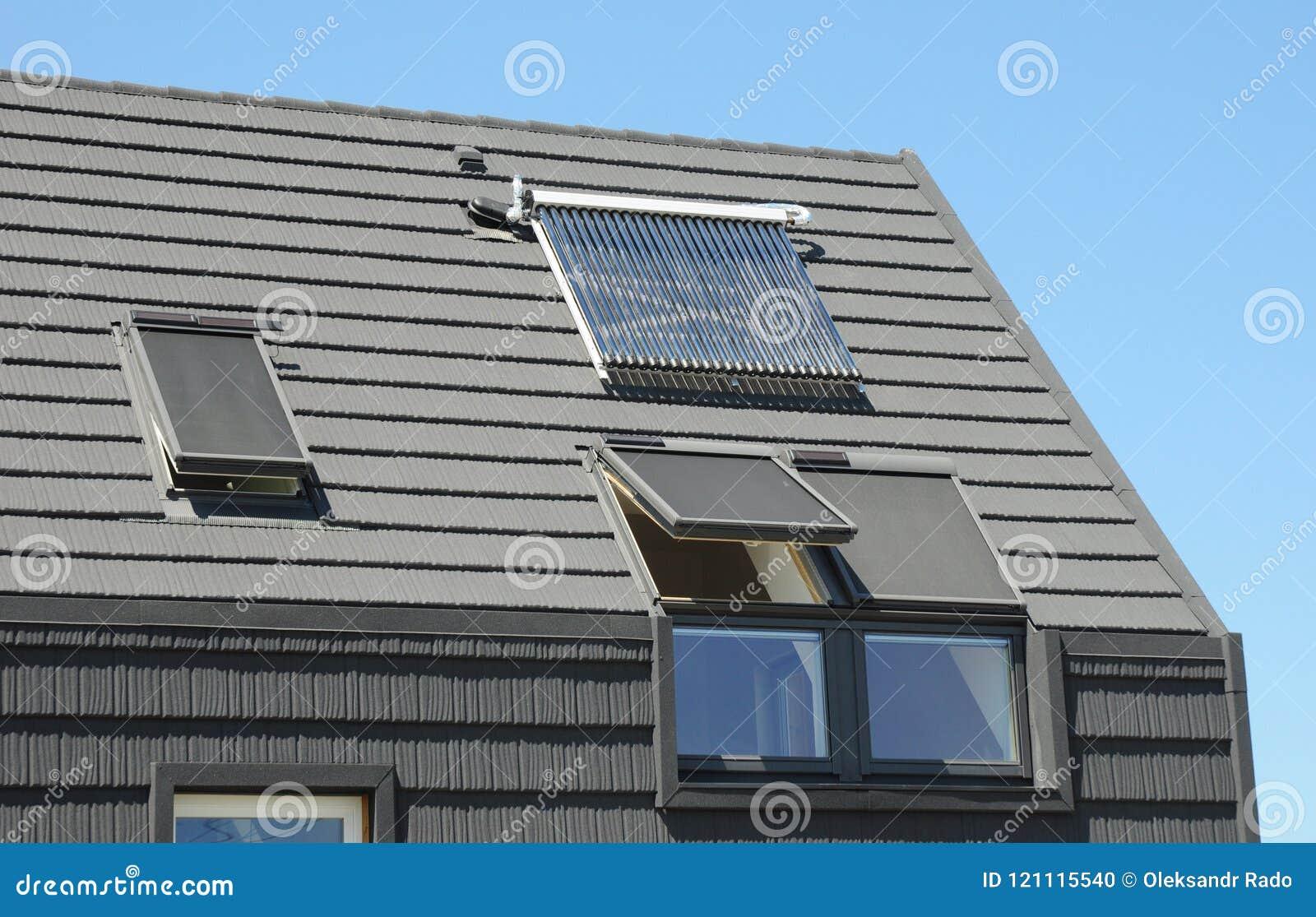 Tetto moderno della soffitta con i pannelli solari, i lucernari e la finestra dei ciechi per protezione del sole e rendimento ene