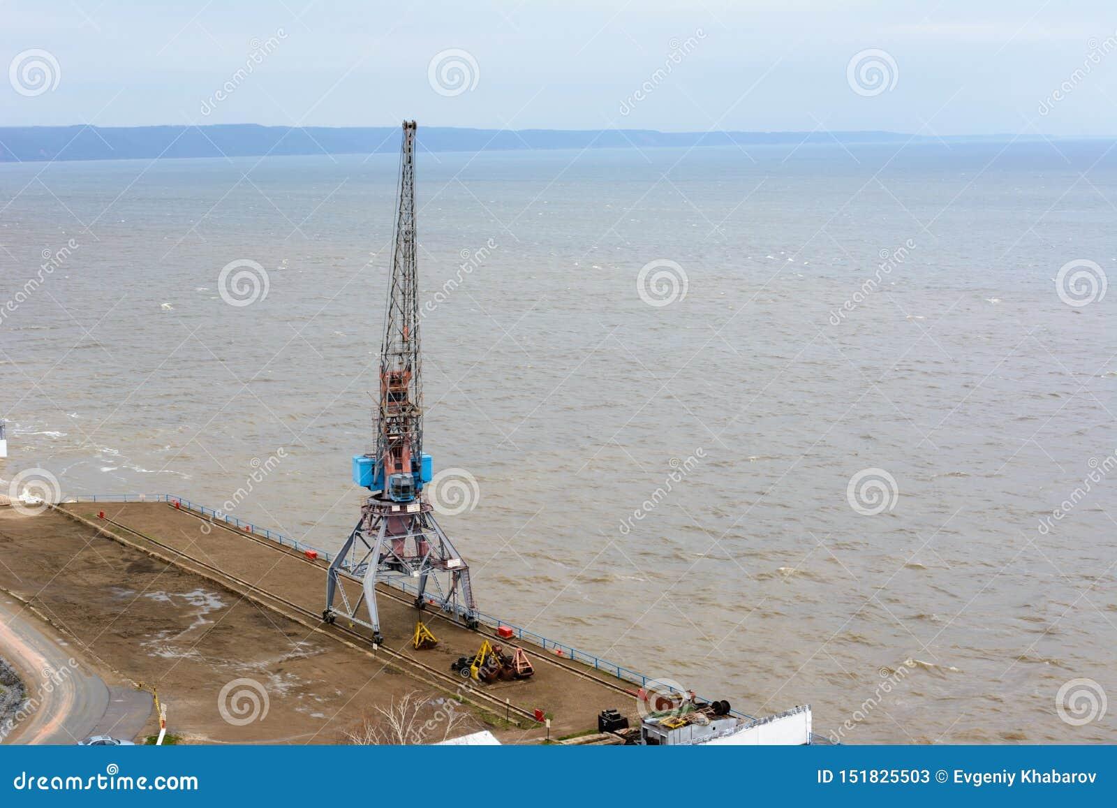 Tetyushi Tatarstan/Ryssland - Maj 2, 2019: Bästa sikt av den tomma industriella pir med lasthamnkranen på skeppsdockan längs