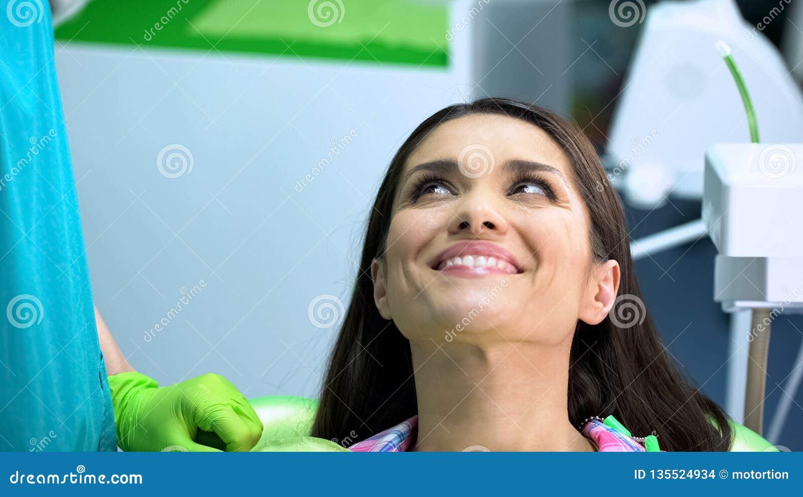 Tevreden cliënt na regelmatig tandonderzoek van mondholte, gezonde tanden