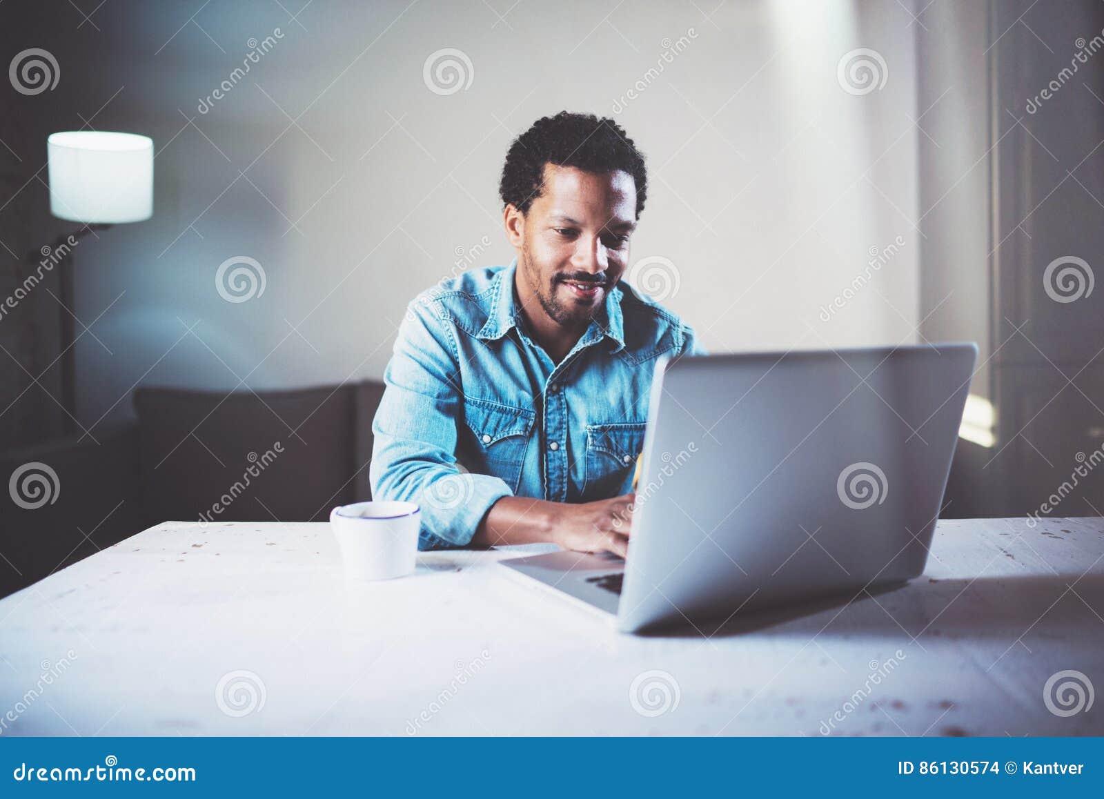 Tevreden gebaarde Afrikaanse mens die laptop met behulp van bij het coworking van studio op de houten lijst Het concept jongeren