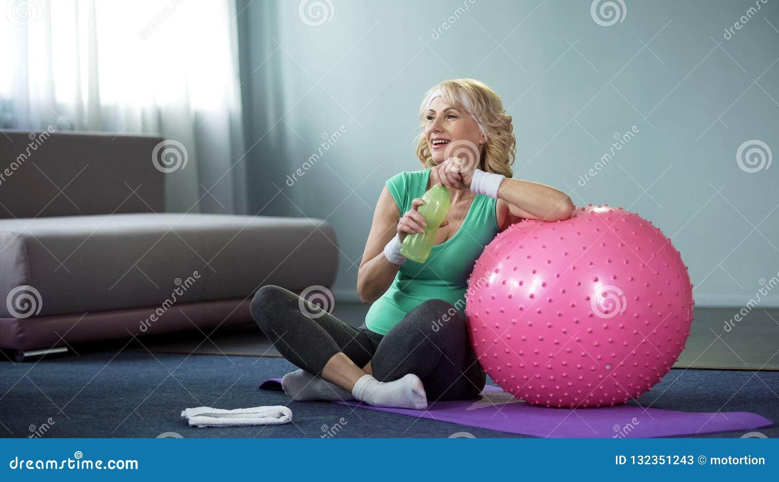 Tevreden hoger wijfje met fles water het ontspannen na training, sport