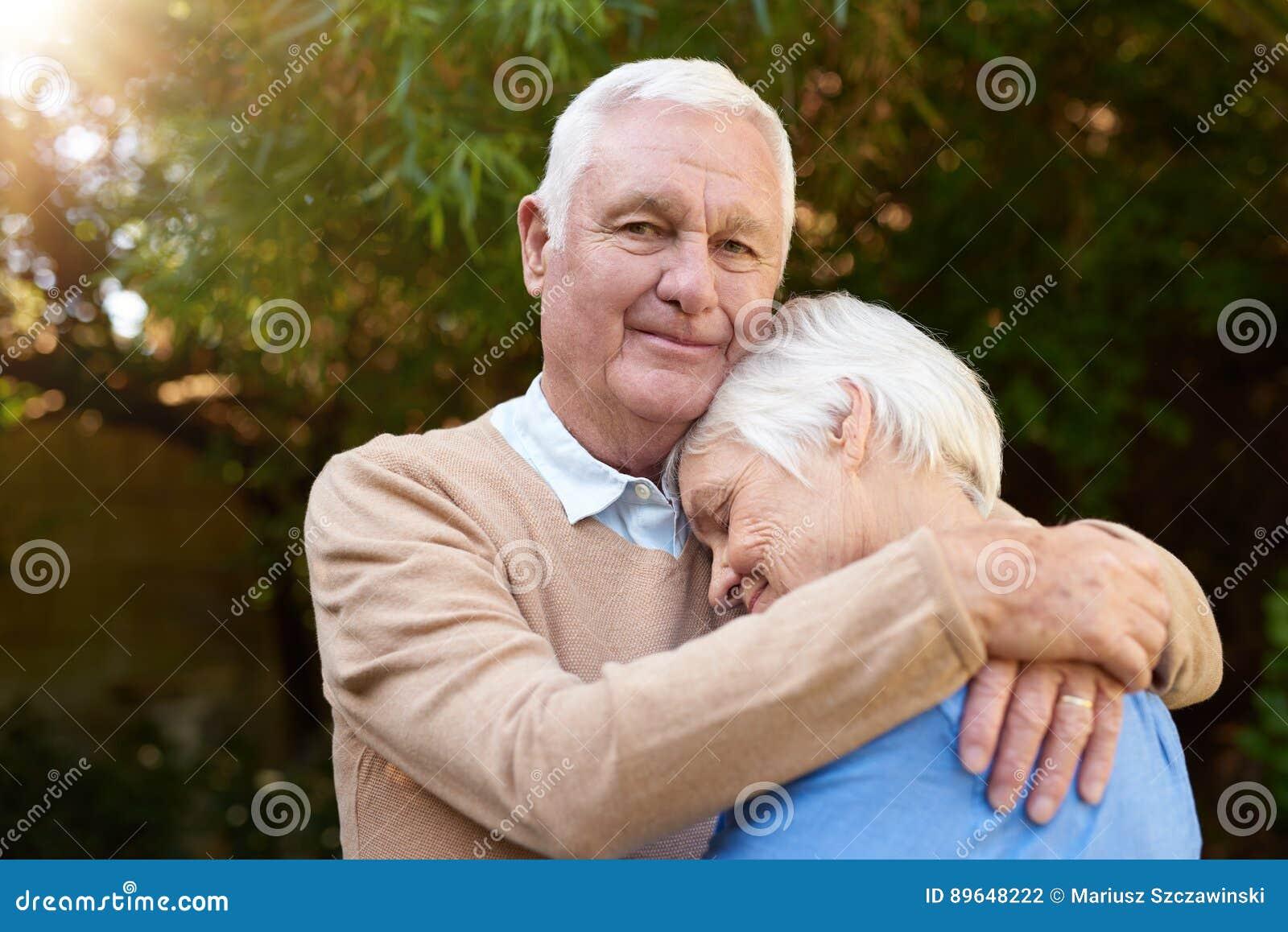 Tevreden hogere mens die affectionately zijn vrouw buiten koesteren
