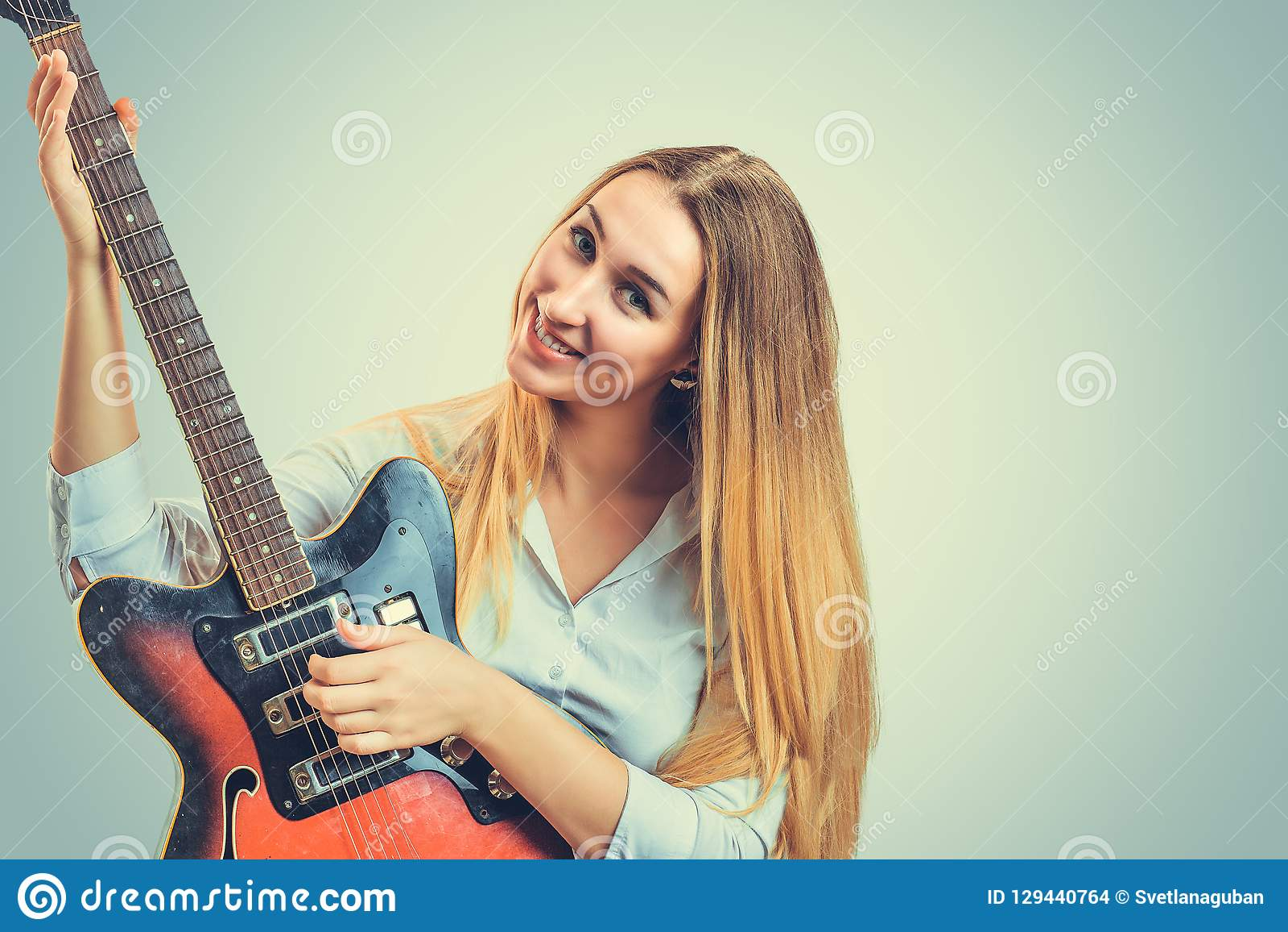 Tevreden vrouw met elektrische gitaar