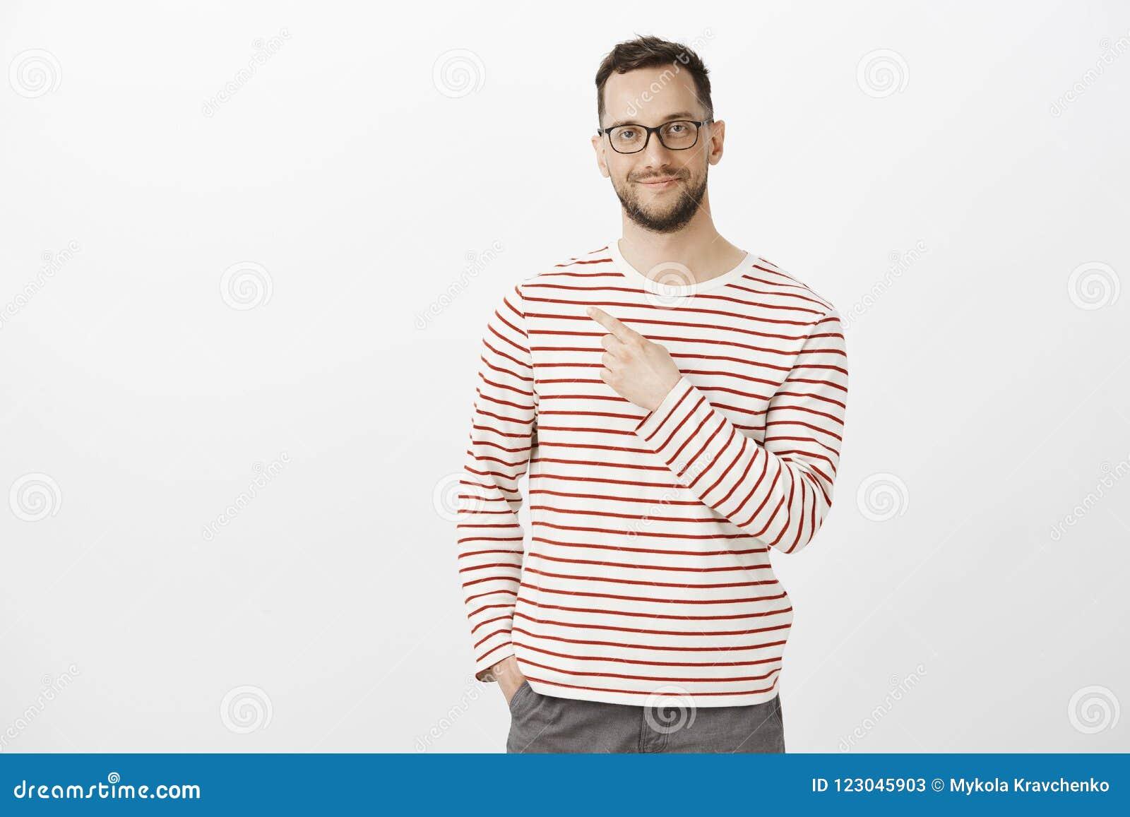 Tevreden zeker mannelijk model met varkenshaar in modieuze eyewear en vrijetijdskleding, die op hogere linkerhoek richten en
