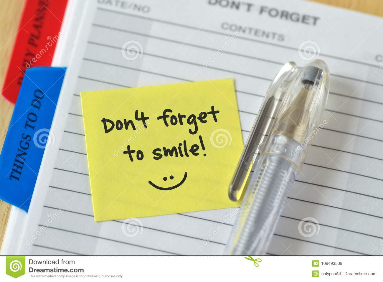 Text don`t forget to smile written on a sticky note over an agen