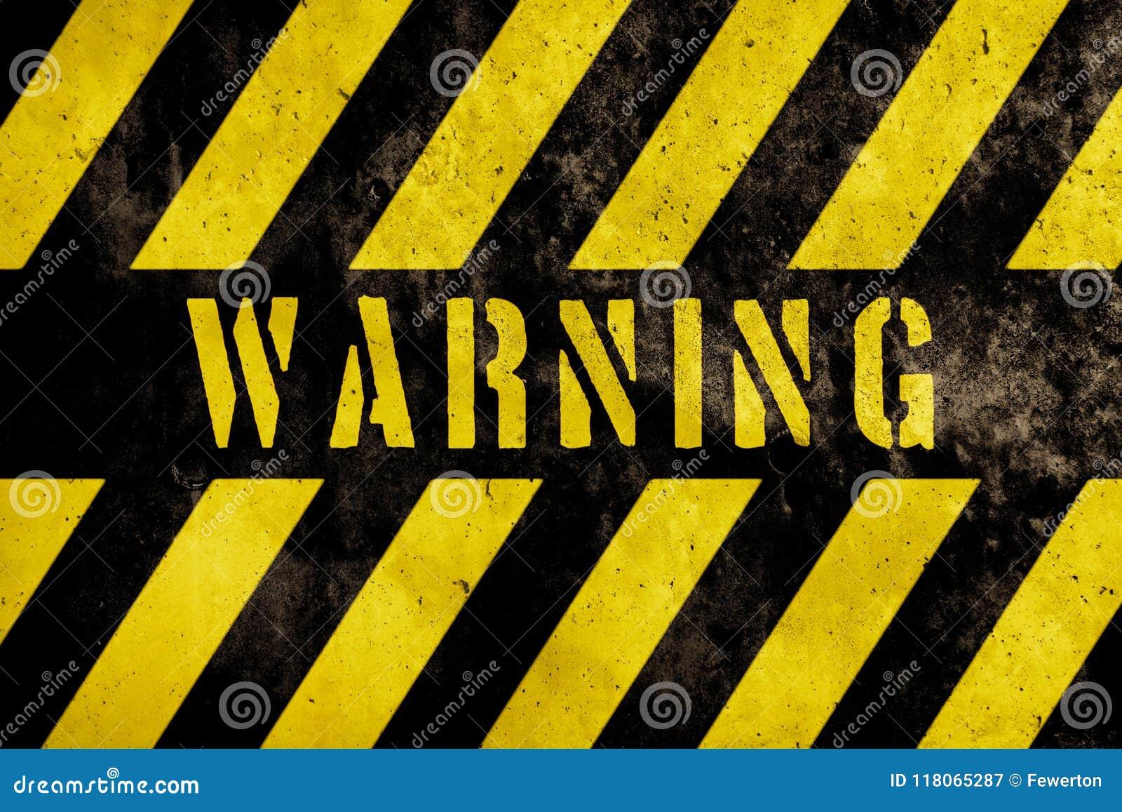 Text för varningstecknet med guling och mörka band som målas över betongväggfasad, texturerar bakgrund