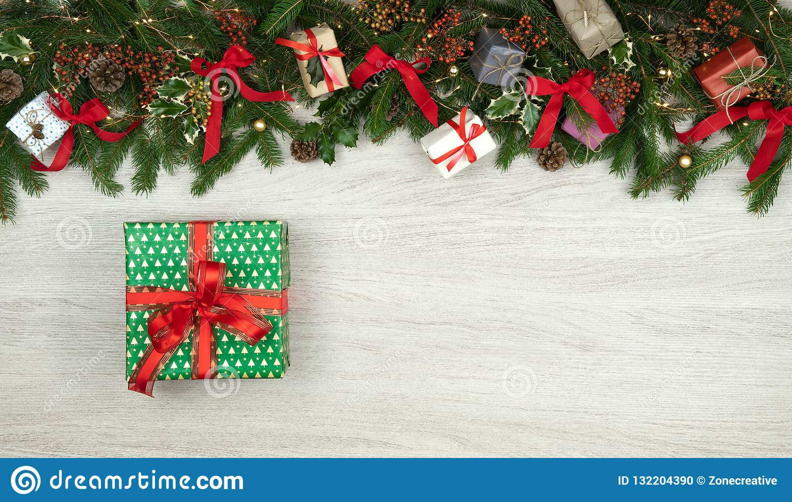 Text or logo empty copy space in vertical top view white wood with pine branches,ribbons, lights and gift present box