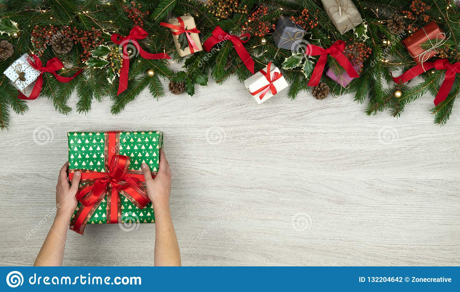 Text or logo empty copy space in vertical top view white wood with pine branches,ribbons,lights,gift present box,hands