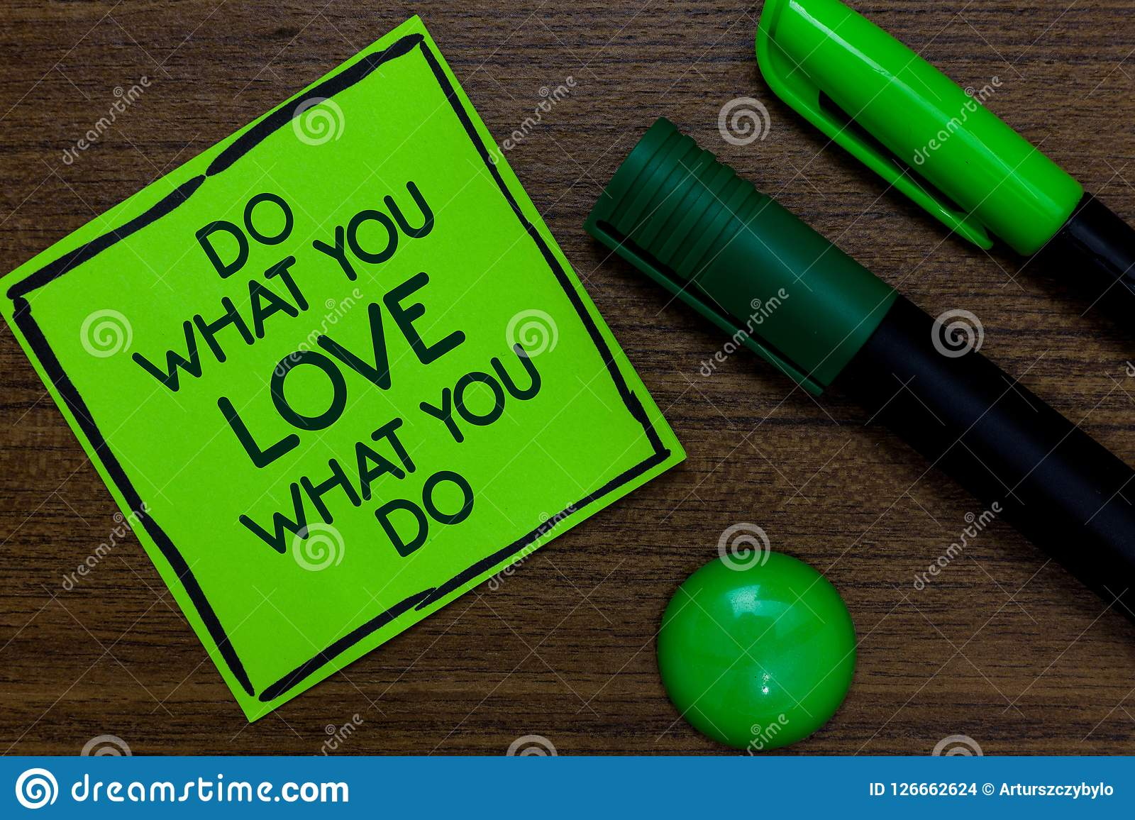 Text sign showing Do What You Love What You Do. Conceptual photo Make things that motivate yourself Passion Written on sticky note. Two markers laid on wooden Stock Images