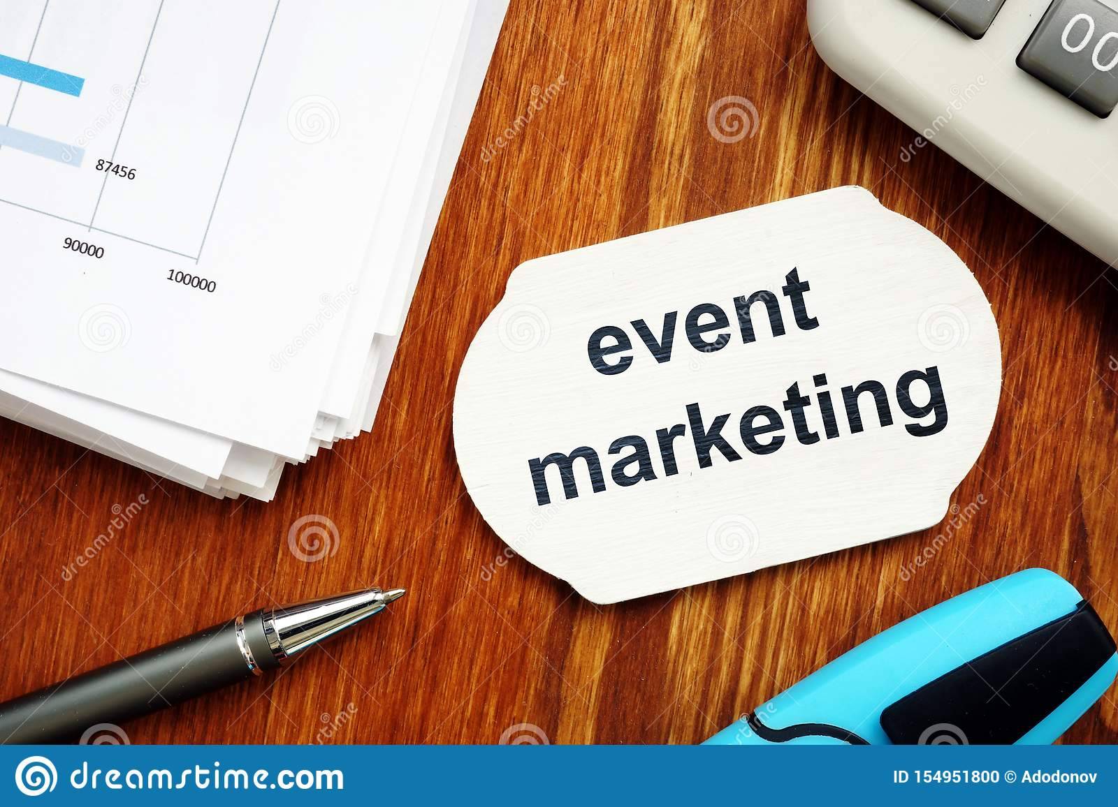 Text sign showing event marketing. The text is written on a small wooden board. Graphs on the paper sheet, pen, keyboard, wooden
