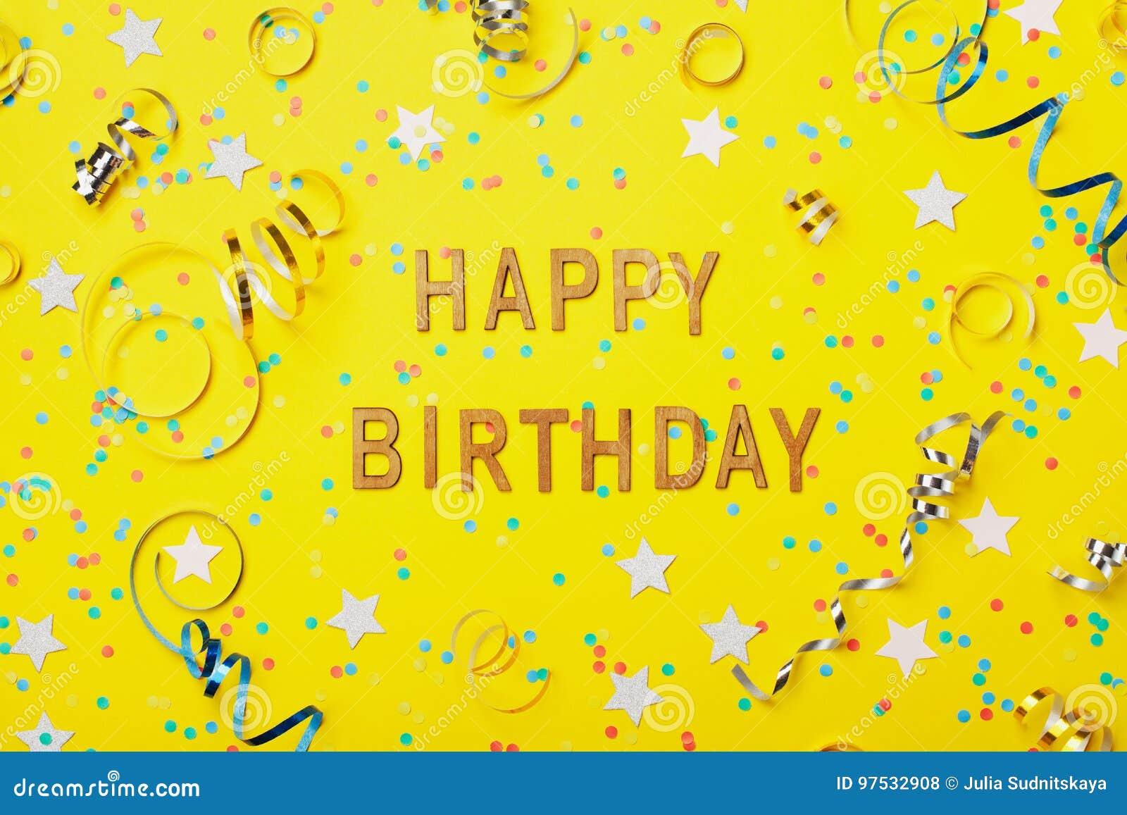 Texte de salutation de joyeux anniversaire décoré des confettis et de la serpentine sur la vue supérieure de fond jaune style pla