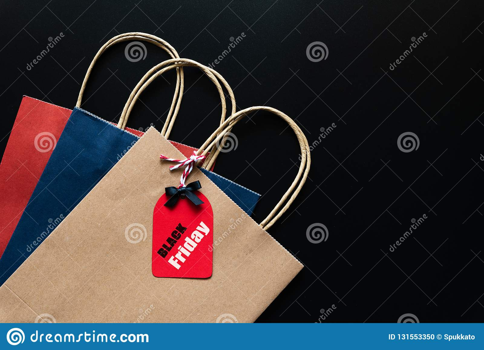 Texte de vente de Black Friday sur une étiquette rouge avec le sac à provisions sur le fond noir Achats en ligne