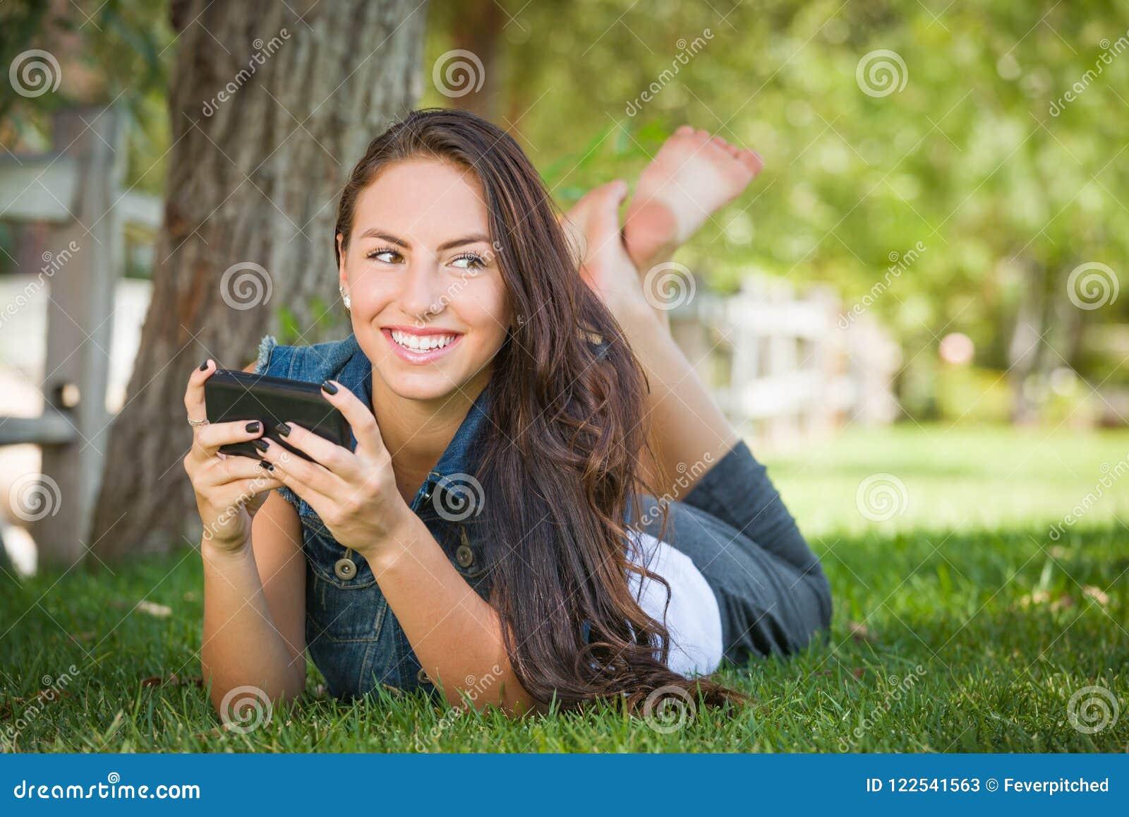 Texting fêmea novo feliz atrativo da raça misturada em sua pilha Pho