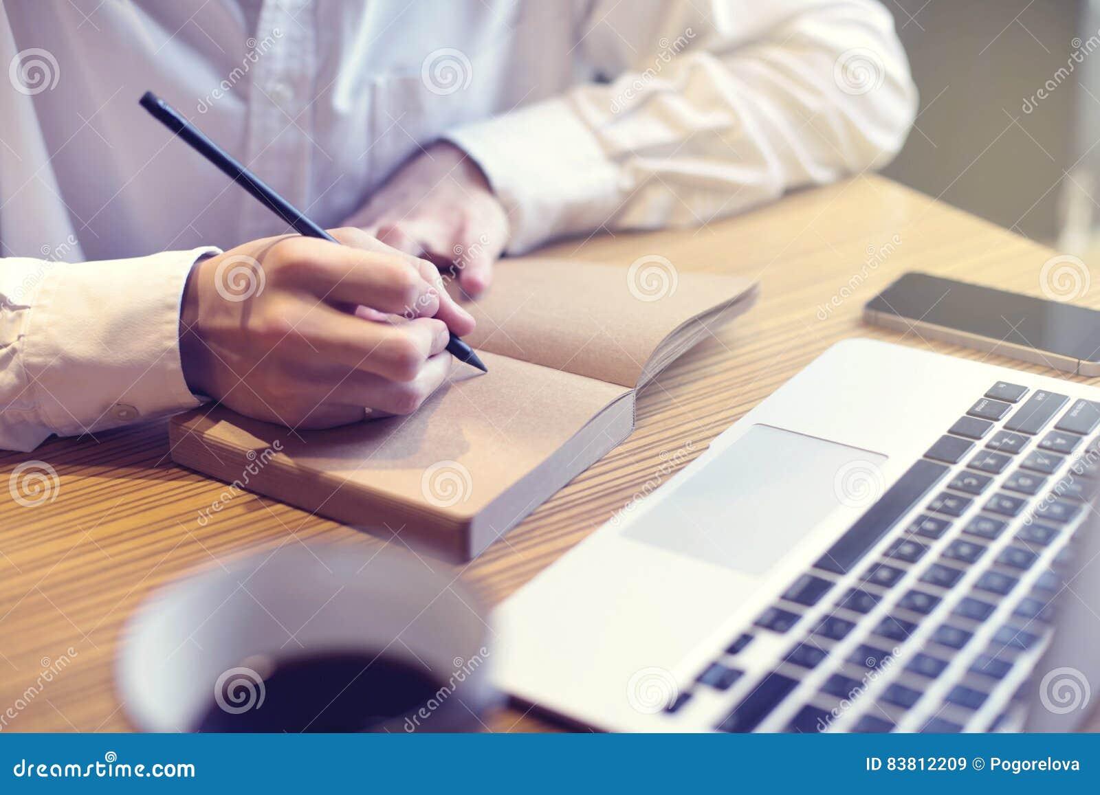 Texto da escrita do homem de negócios no caderno e olhar no portátil aberto no café, espaço detrabalho do público Tendo a café-ru