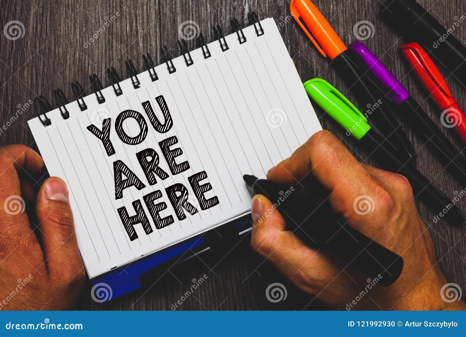 Texto da escrita da palavra você está aqui O conceito do negócio para este é sua terra arrendada da mão do sistema de navegação m