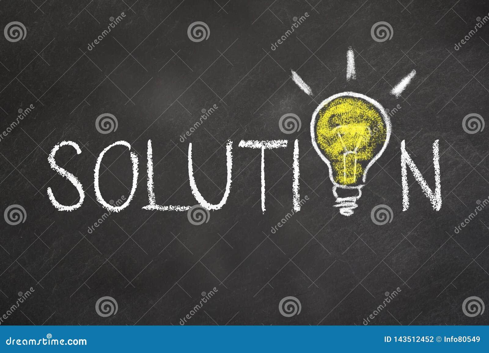 Texto de la 'solución 'con una bombilla de la idea en el tablero de tiza