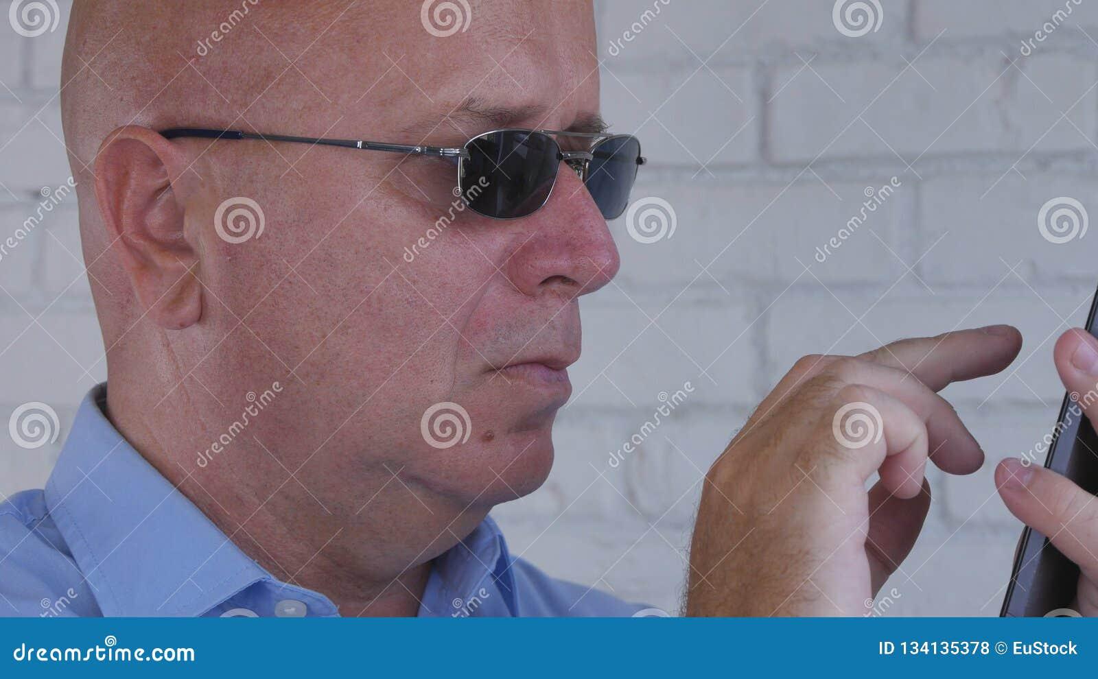 Texto de Wearing Black Sunglasses del hombre de negocios usando el teléfono celular