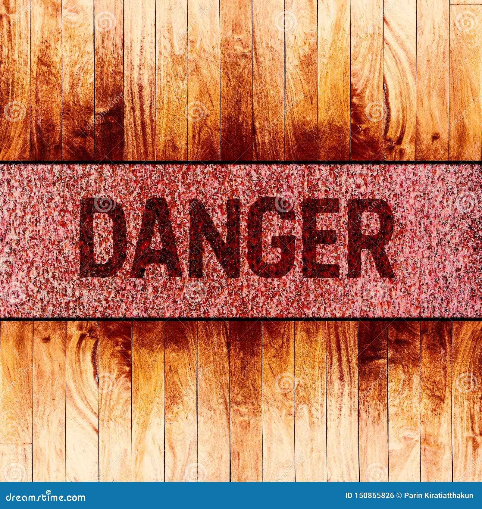 Texto do sinal de aviso do perigo no fundo oxidado do metal