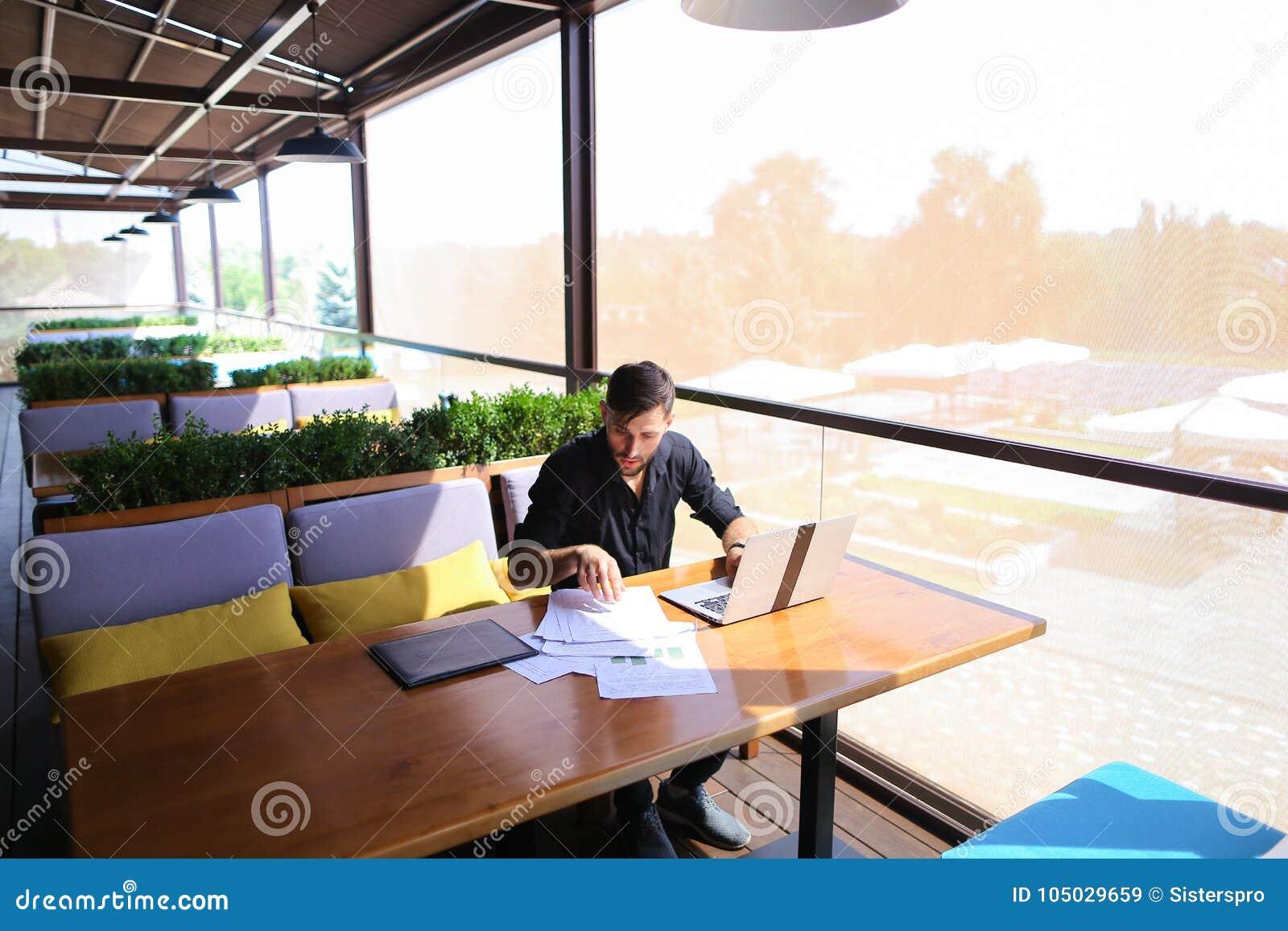 Texto independiente de la reescritura del redactor de anuncios en el ordenador portátil en la tabla del café