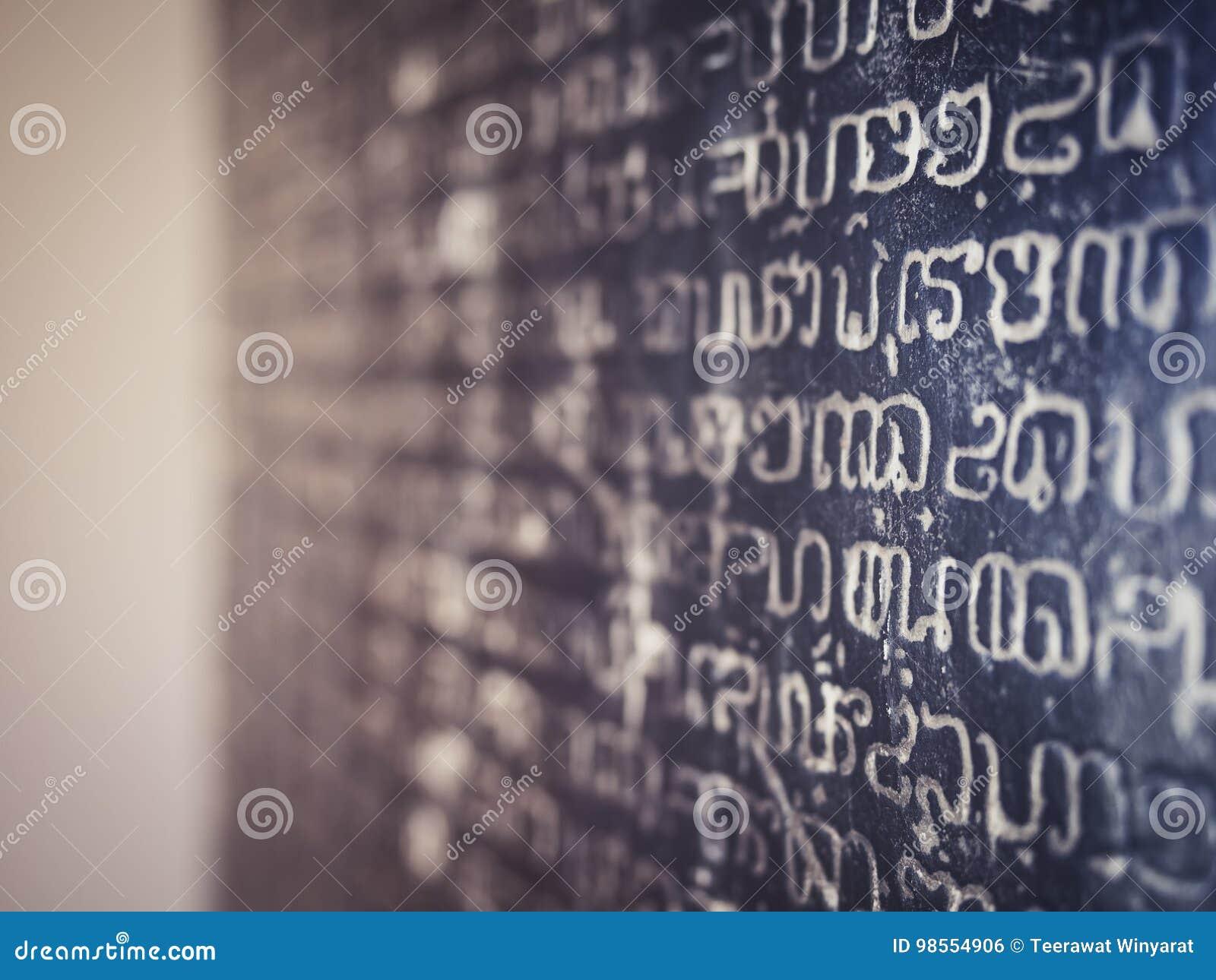 Textur för bokstav för historia för steninskriftalfabet forntida