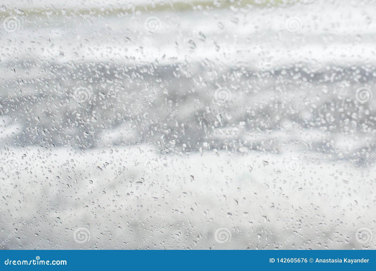 Textura branca e cinzenta de gotas do bokeh no vidro
