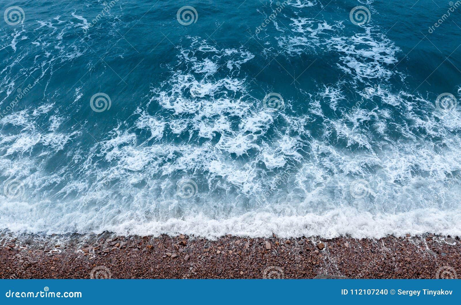 Textura da faculdade criadora da água Nadada das ondas à costa rochosa Vista superior