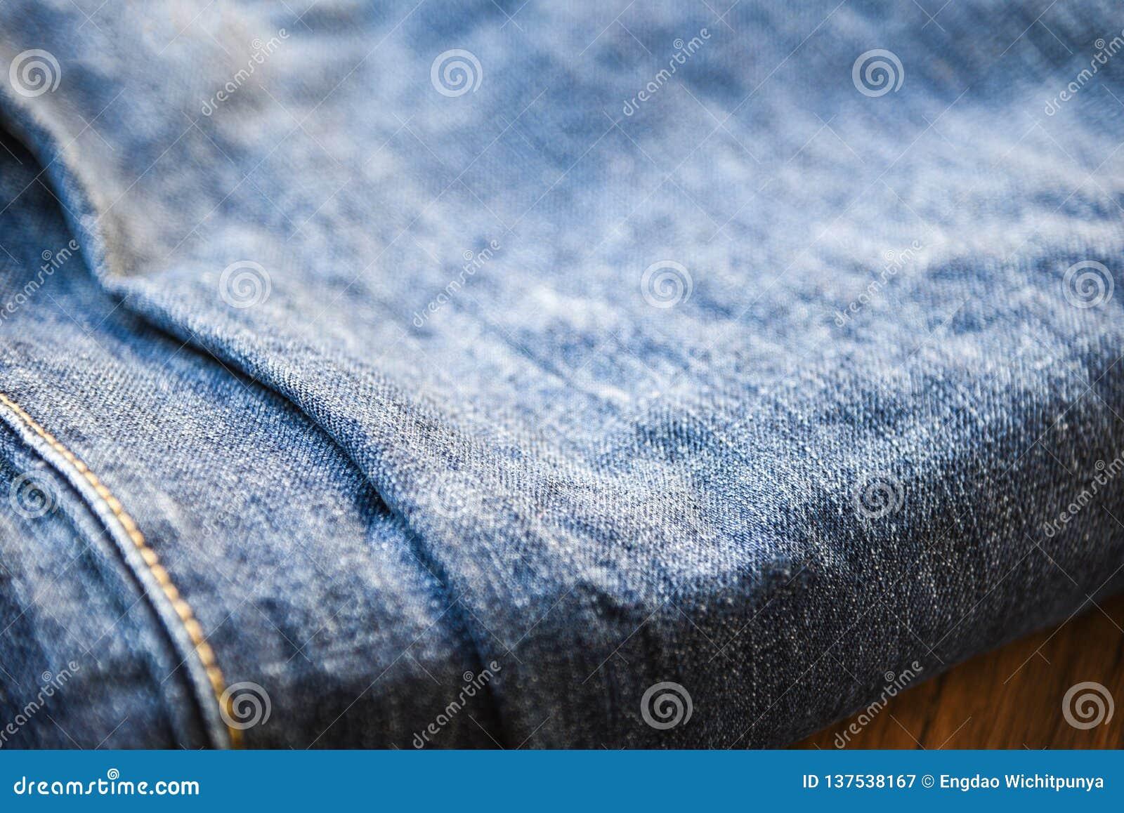 Textura das calças de brim da sarja de Nimes da roupa perto acima da dobra do teste padrão de calças de ganga no fundo de madeira