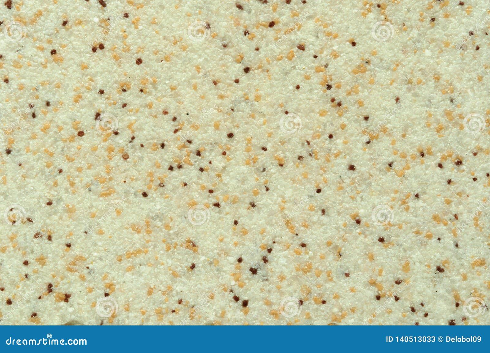 Textura de la capa de cerámica beige con las inclusiones oscuras