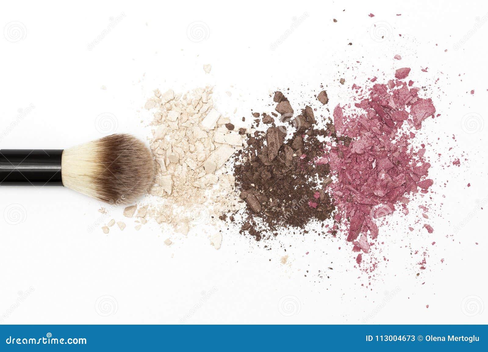 Textura de la sombra de ojos y cepillo cosmético en el fondo blanco