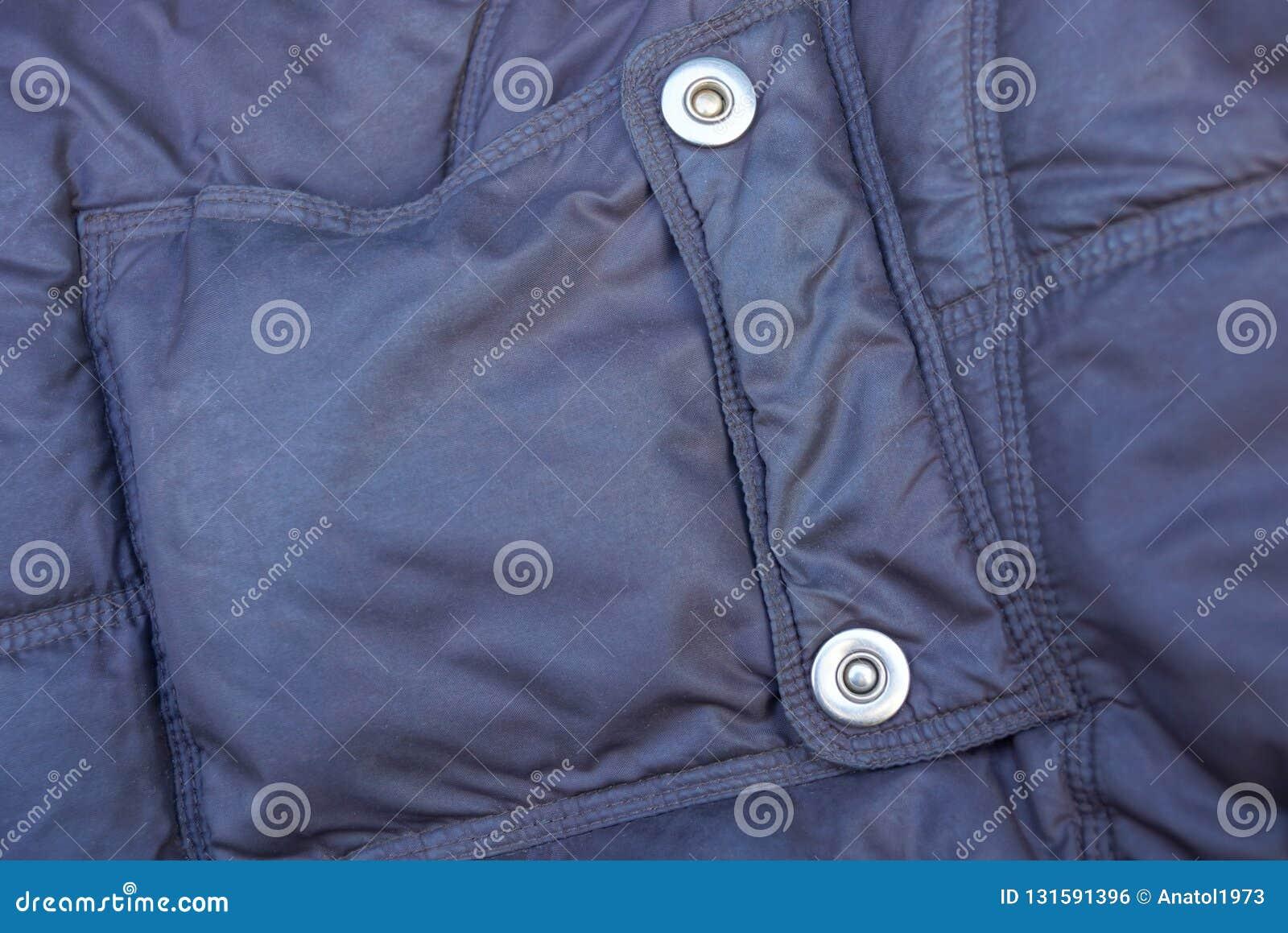 Textura de la tela de Brown del bolsillo con los remaches del metal en la ropa sintética