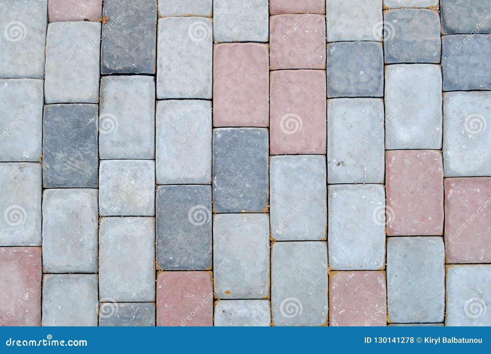 Textura de las losas de la piedra concreta rectangular gris en el camino con las costuras Los antecedentes