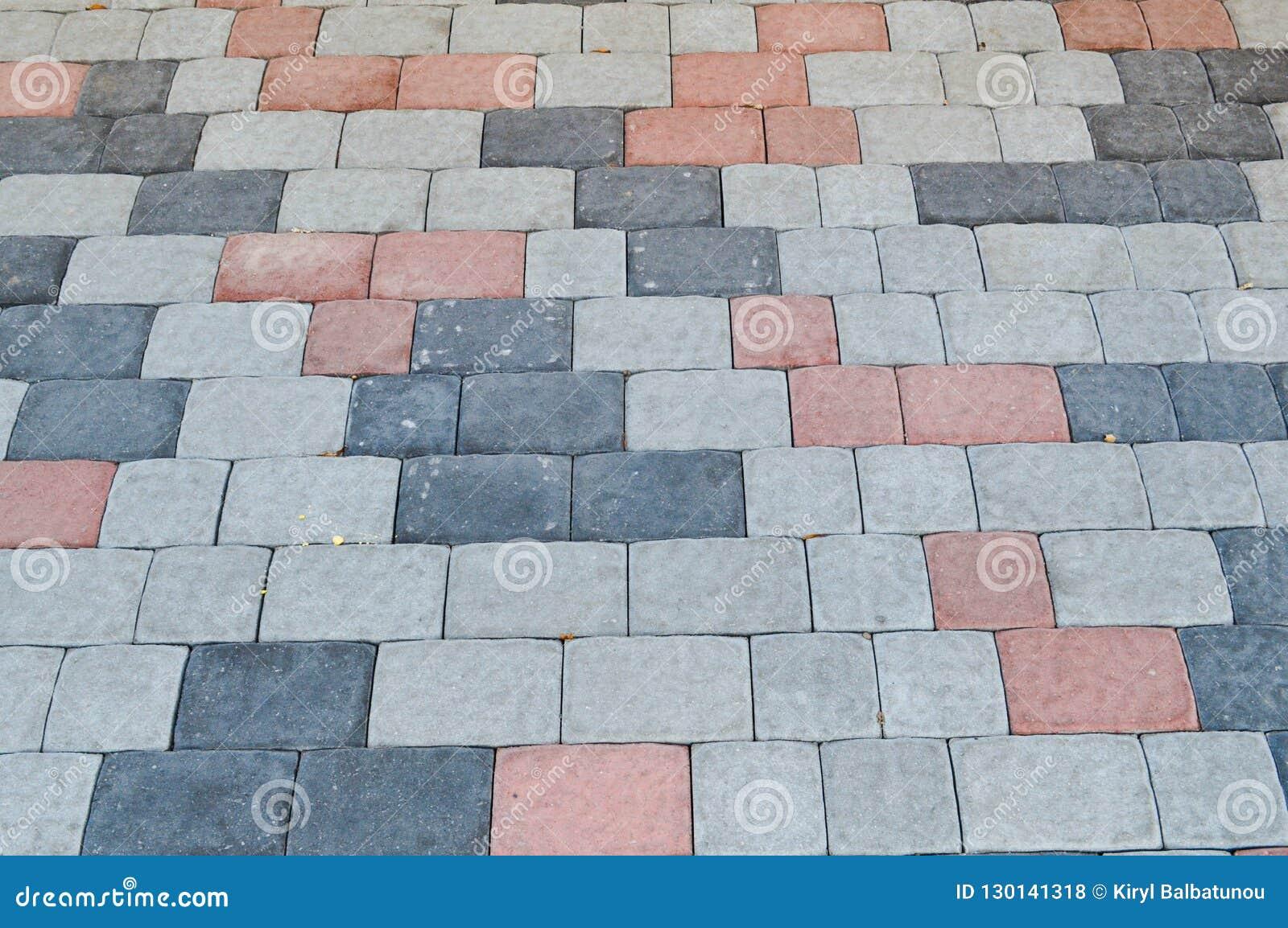 Textura de pavimentos da pedra concreta retangular cinzenta na estrada com emendas O fundo