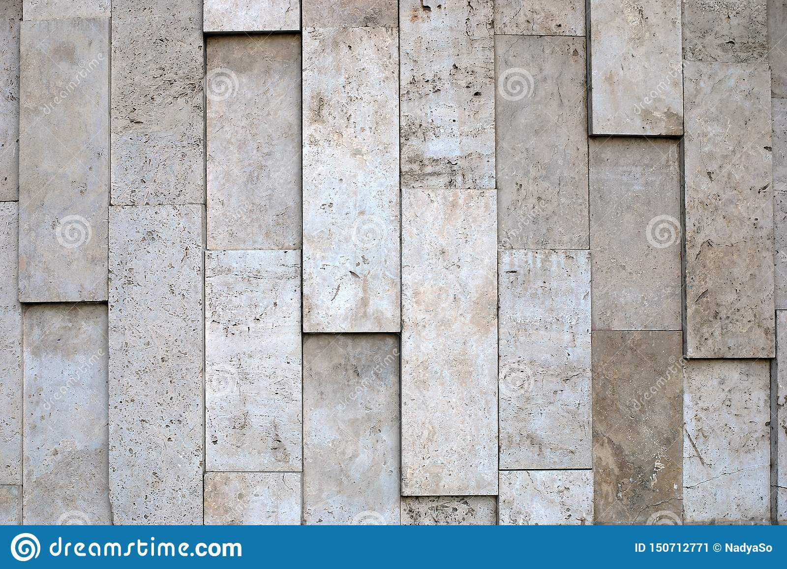 Textura desigual natural da parede de pedra do material poroso das cores bege da escala