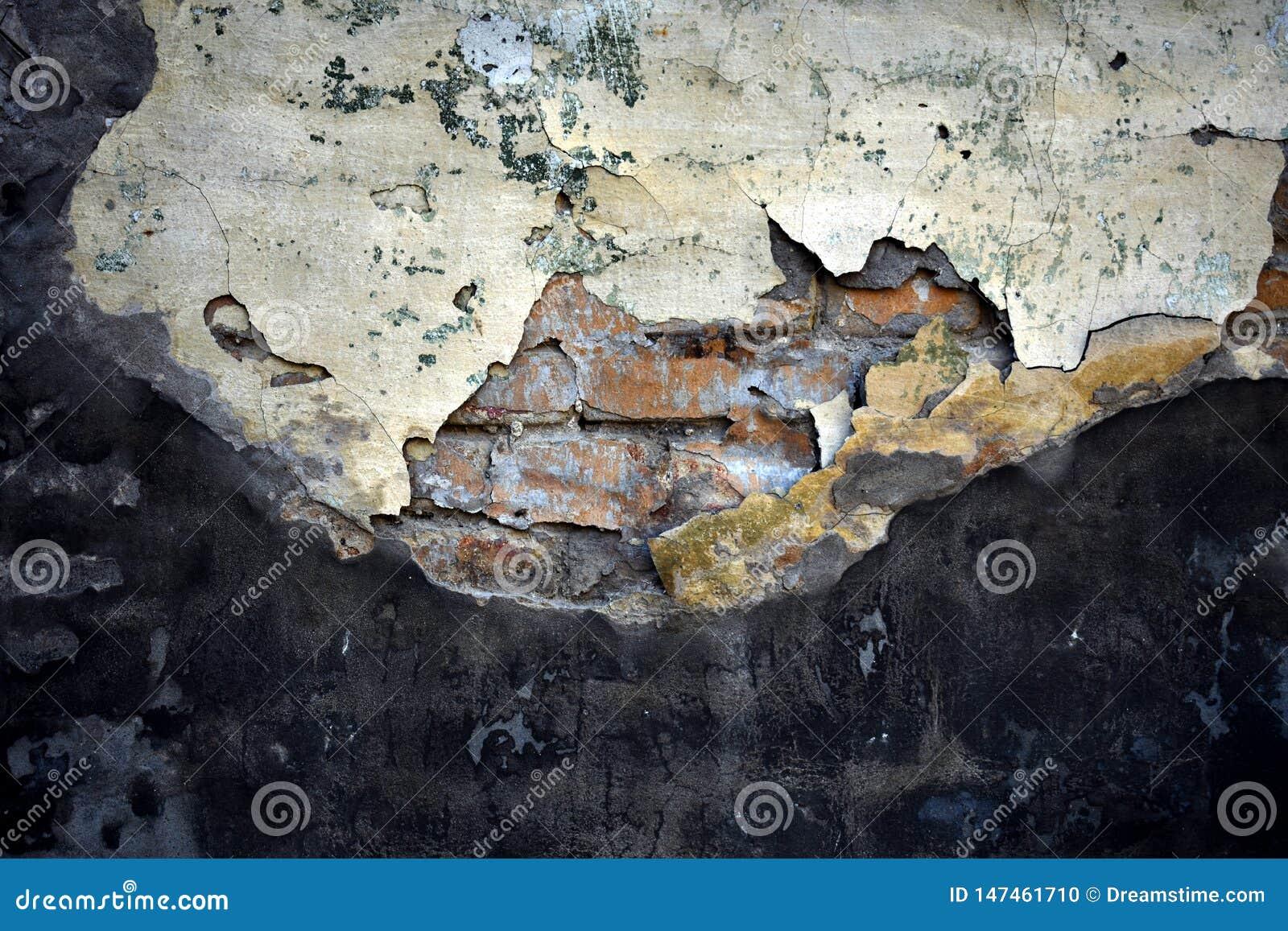 Textura do cimento quebrado velho sobre a parede de tijolo