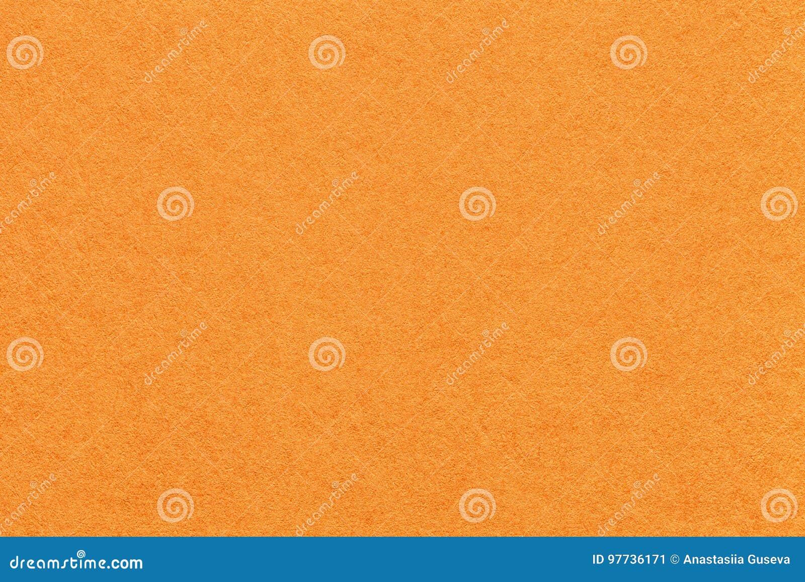 Textura do fundo de papel alaranjado brilhante velho, close up Estrutura do cartão denso da cenoura