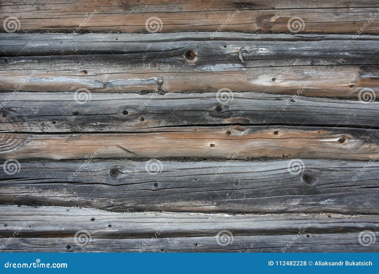 Textura do fundo de uma parede de logs e de placas de madeira idosos