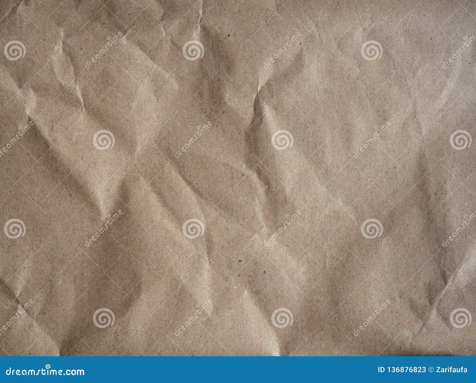 Textura do papel amarrotado do ofício, superfície de papel velha para o fundo