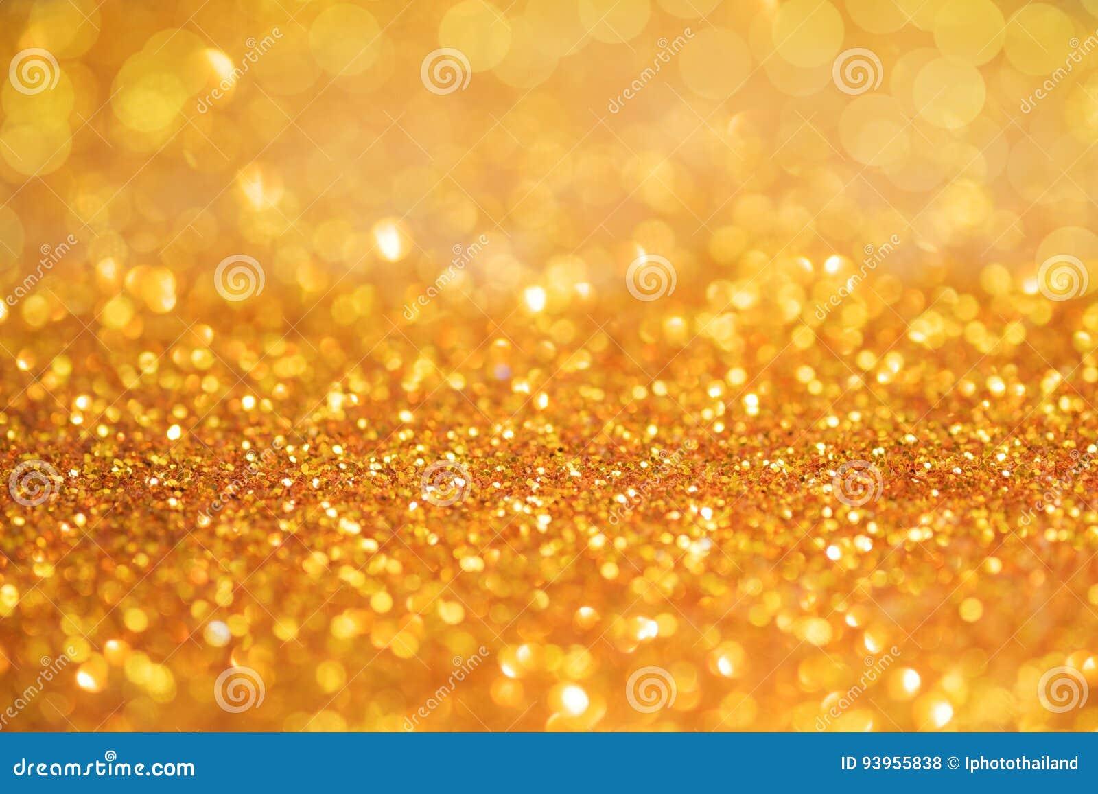 A textura ou o brilho claro do bokeh do ouro iluminam o backgrou festivo do ouro